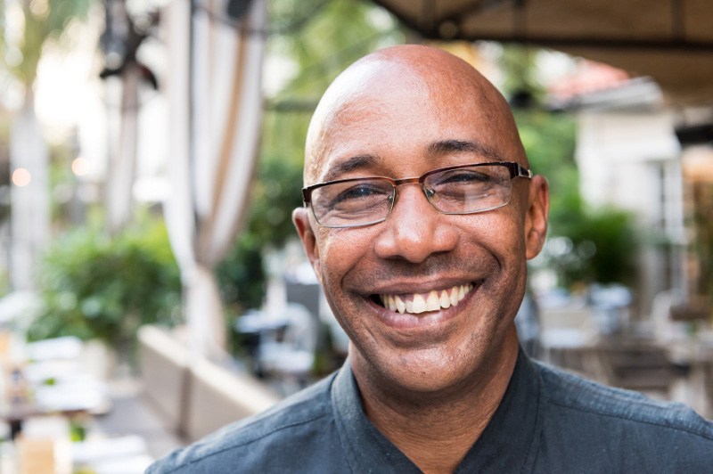 Black man in street smiling with glasses on